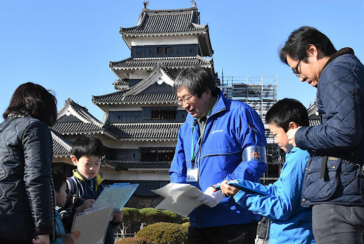 クイズに答えながら松本城を巡る参加者ら