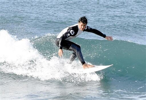 水しぶきを上げながら軽快に波に乗るサーファー=12月1日、福井県坂井市の三国サンセットビーチ