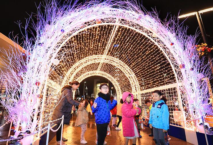 光のゲートをくぐる子どもたち=富山駅前