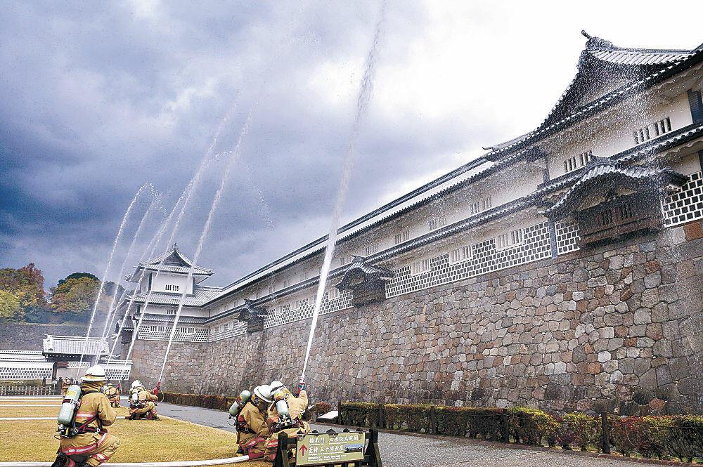 五十間長屋に向けて放水する消防署員=金沢城公園