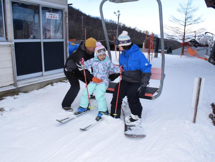 オープンした八千穂高原スキー場のリフトに乗り込む親子