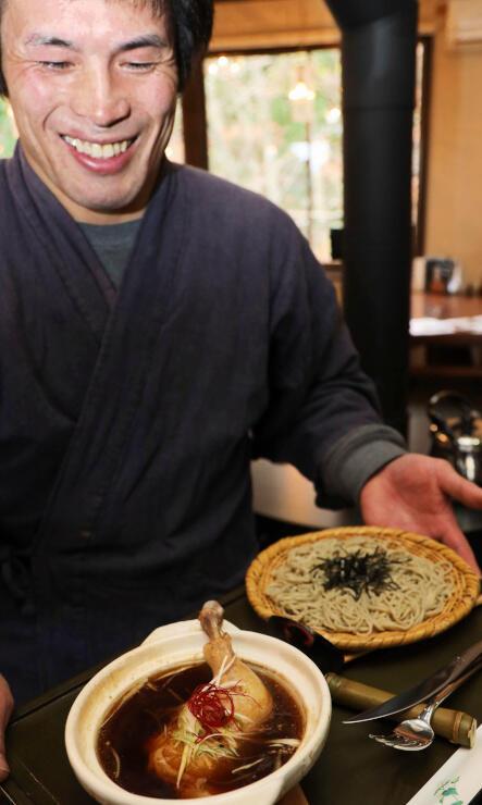 骨付きの鶏肉を煮込んだスープでそばを食べる新商品をPRする竹内さん