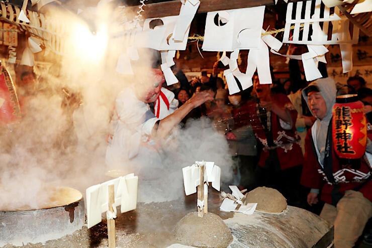 煮えたぎる湯を素手ではねかける「湯切り」をする「大天狗」=7日午後11時28分、飯田市南信濃小道木の熊野神社