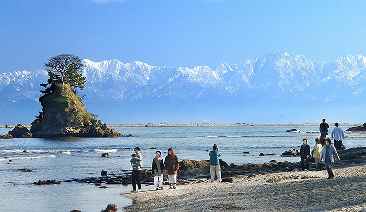 富山湾越しにくっきりと見えた立山連峰。左は女岩=雨晴海岸