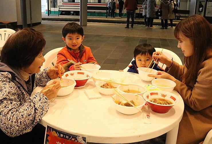 鍋料理などを食べて温まる家族連れ