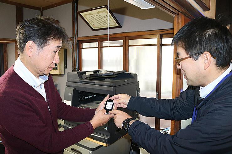 高岡市職員(右)から翻訳機の説明を受ける塩田代表