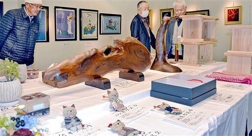 久里洋二さんの絵画など多彩な作品を品定めする来場者=12月9日、福井県鯖江市文化の館