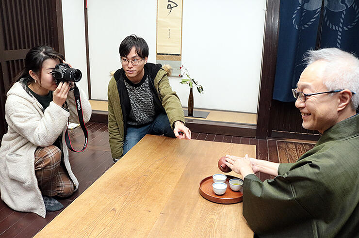 ポスター制作に向け、栗林さん(右)を撮影する学生