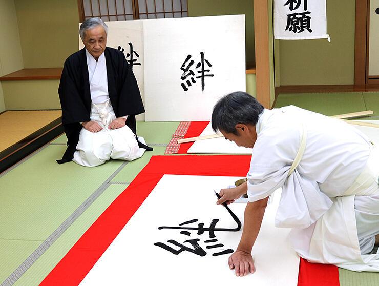 大絵馬に力強く「絆」の文字をしたためる上田さん(右)と見守る関支部長=高岡市古城