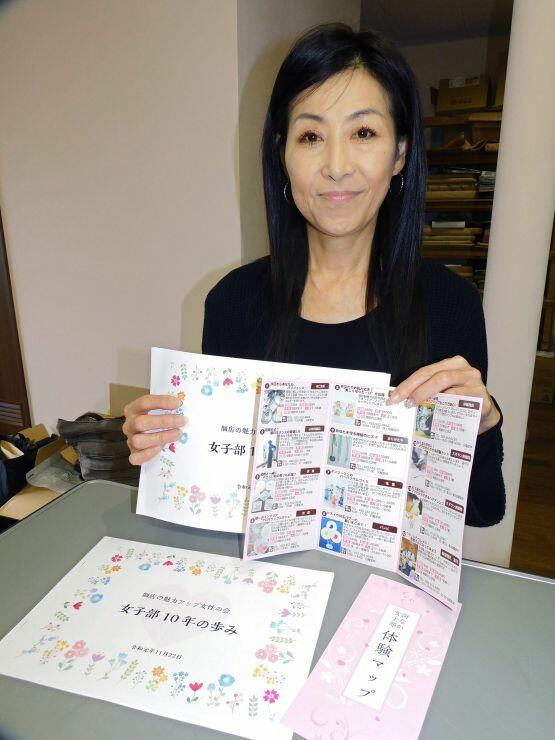 記念冊子と体験型講座のマップを手にする室川亜紀会長=糸魚川市