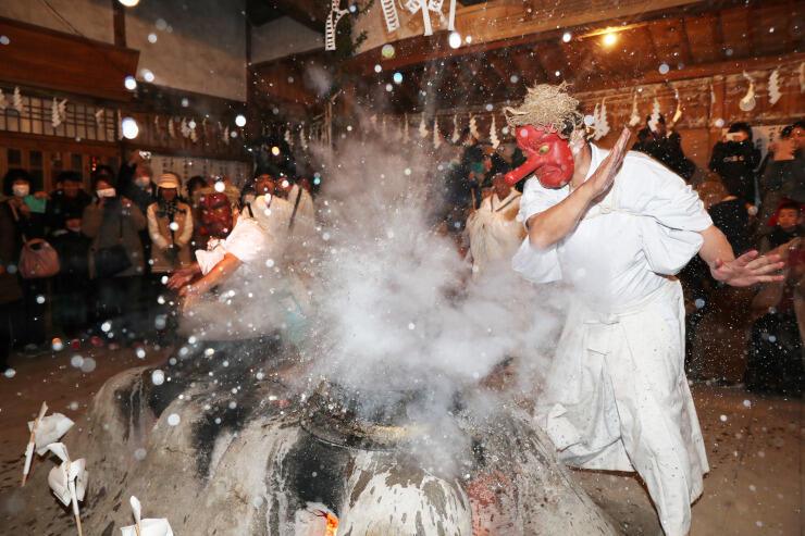 面を着けた氏子が熱湯を素手ではじき、クライマックスを迎えた上村上町の霜月祭り=12日午前5時54分、正八幡宮