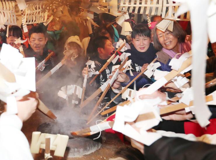 湯木を持って湯立てに加わる氏子や参拝者ら=7日午後9時25分、南信濃小道木の熊野神社
