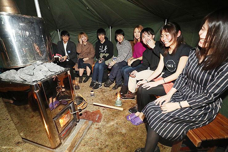 ストーブで温められたテントサウナに入る人たち=富山城址公園