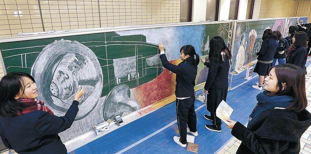 黒板アートの制作を進める金沢美大の学生と桜丘高の生徒=金沢駅もてなしドーム地下広場