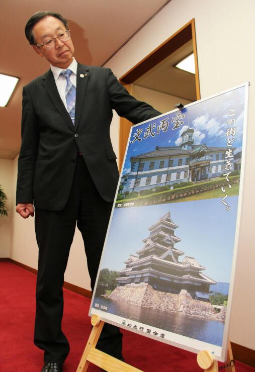 田中さんはポスターの旧開智学校校舎の写真を見つめ「高楼の掃除が狭くて大変だった」などと懐かしんだ