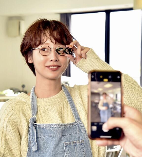 購入した眼鏡を掛け、作ったストラップを手に写真に納まる石田さん=12月13日、福井県鯖江市のめがねミュージアム
