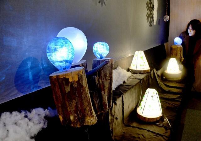 温かな光を放つガラスランプ展=12月13日、福井県小浜市後瀬町の福井新聞小浜支社コミュニティーホール