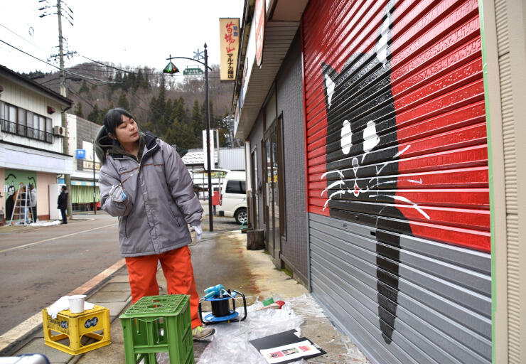 森宮野原駅前の店舗のシャッターに黒猫を描く長野大生