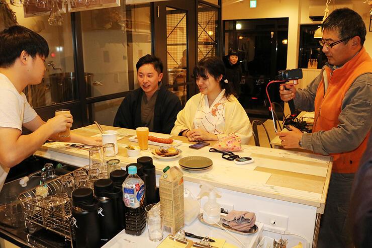 和服姿でクラフトビールと料理を注文する台湾のカップル。右はツアーの様子を撮影する稲垣さん
