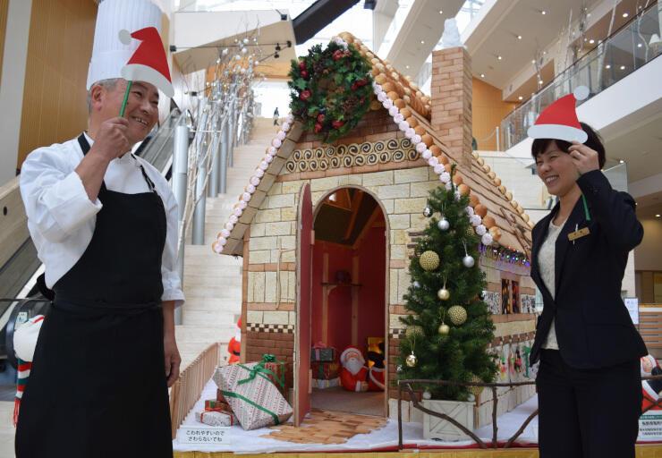 パティシエの森山さん(左)らが菓子とパンで作ったサンタの家。記念撮影用にサンタの帽子なども用意した