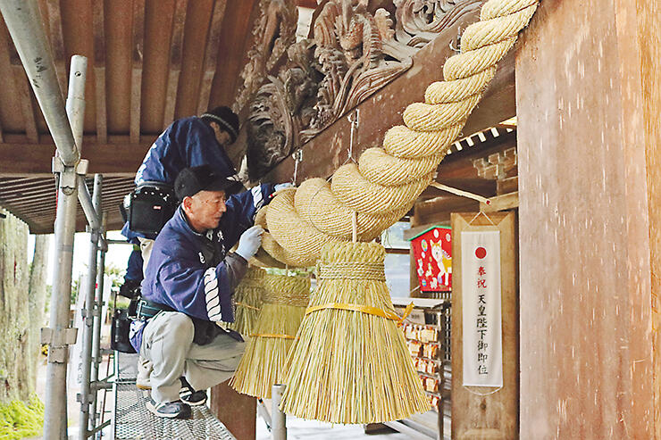 拝殿前のしめ縄を取り付ける職人
