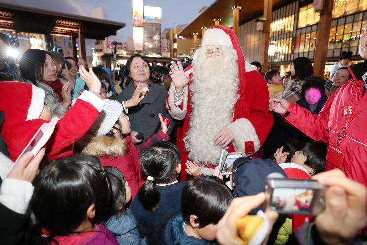 フィンランドからやって来たサンタクロース。子どもたちが手を振って出迎えた=18日午後4時52分、長野市のJR長野駅前