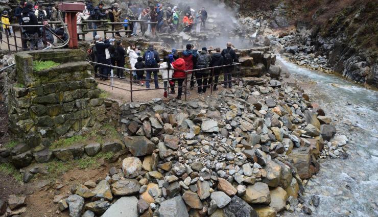 温泉に入る猿を見物する観光客。手前の石積みなどの応急復旧工事がほぼ終了した=17日、地獄谷野猿公苑