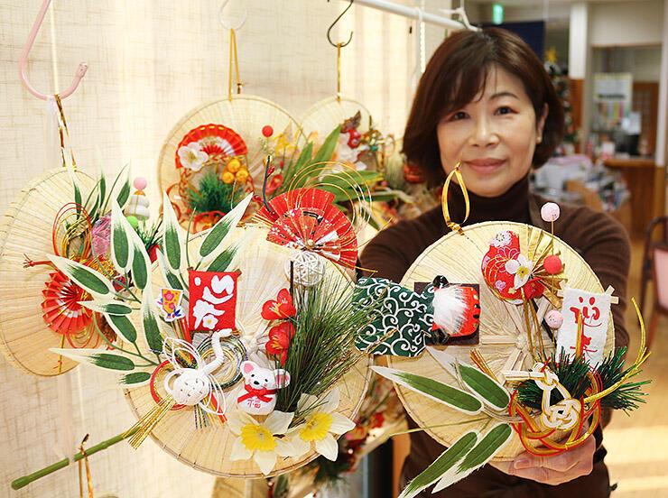 菅笠を使った正月飾りをPRする店員