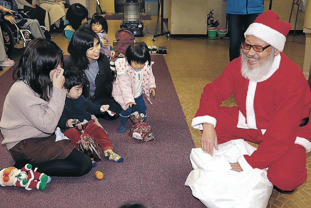 子どもにプレゼントを配る上出さん(右)=加賀市の山中児童センター