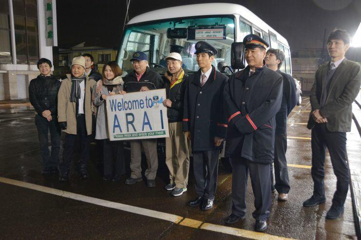 バスの到着を新井駅前で歓迎した関係者たち=18日、妙高市