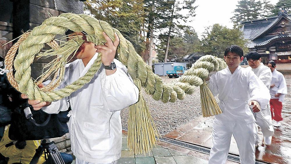 神門のしめ縄を取り替える神職=尾山神社