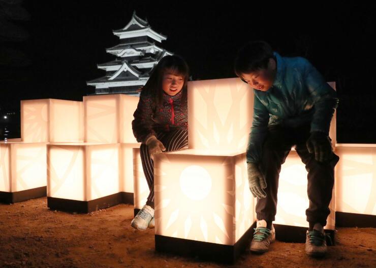 松本城を背に設置した光のオブジェを見る子どもたち