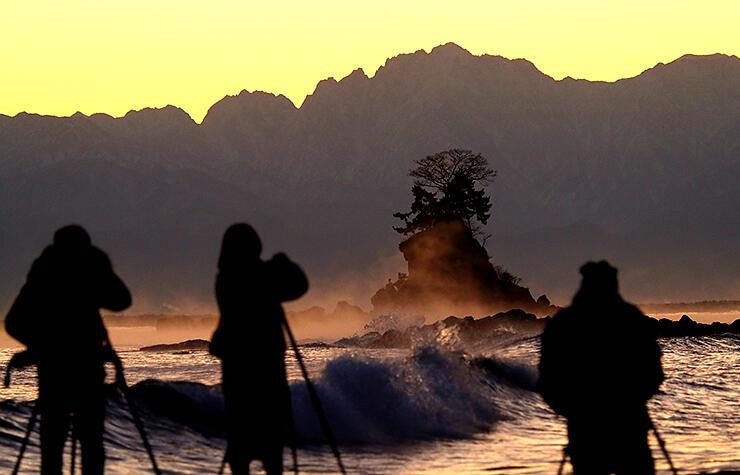 女岩(中央奥)周辺に立ち上った気嵐 =25日午前6時40分ごろ、雨晴海岸