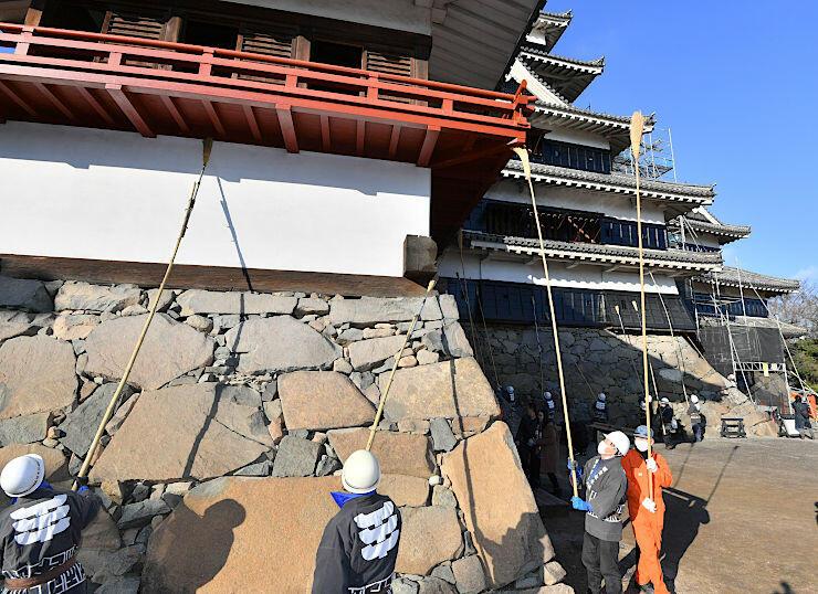 長い柄のほうきですすを払う松本城管理事務所の職員ら