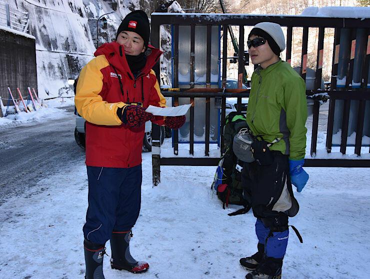 登山計画書を確認する救助隊員(左)と登山者