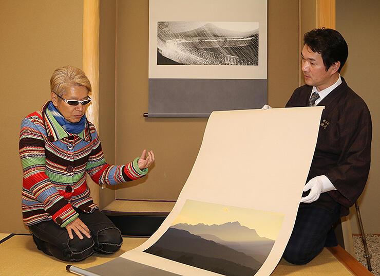 軸装した写真を眺めながら、個展に向け岩崎さん(右)と打ち合わせするテラウチさん=富山市内