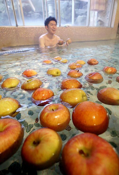 湯船に浮かぶリンゴの香りを楽しむ宿泊客
