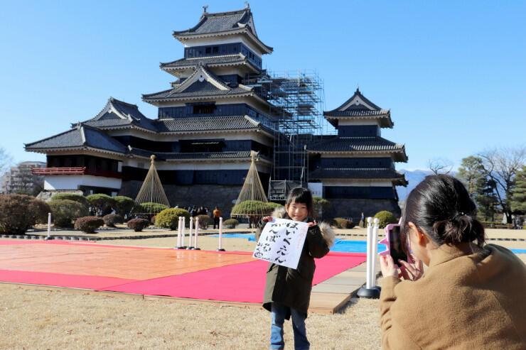 松本城を背に書き初めの紙を持って記念撮影する親子=1日
