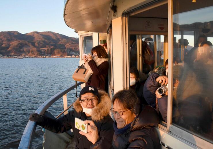 竜宮丸から初日の出を撮影する乗客