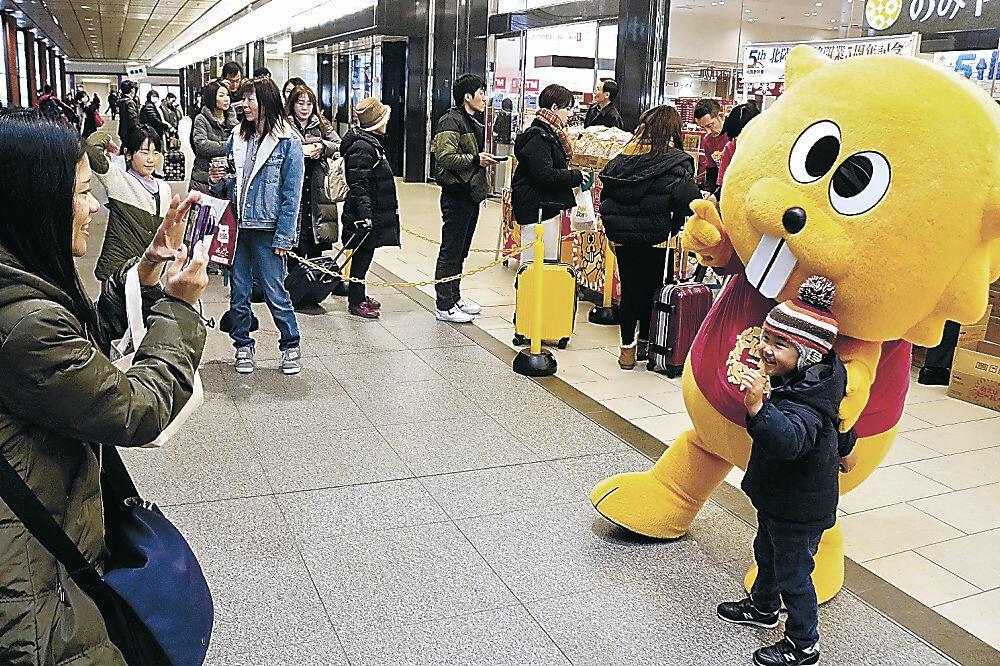 ビーバーのキャラクターと記念写真を楽しむ親子連れ。販売会では大勢の人が「白えび味」を買い求めた=JR金沢駅