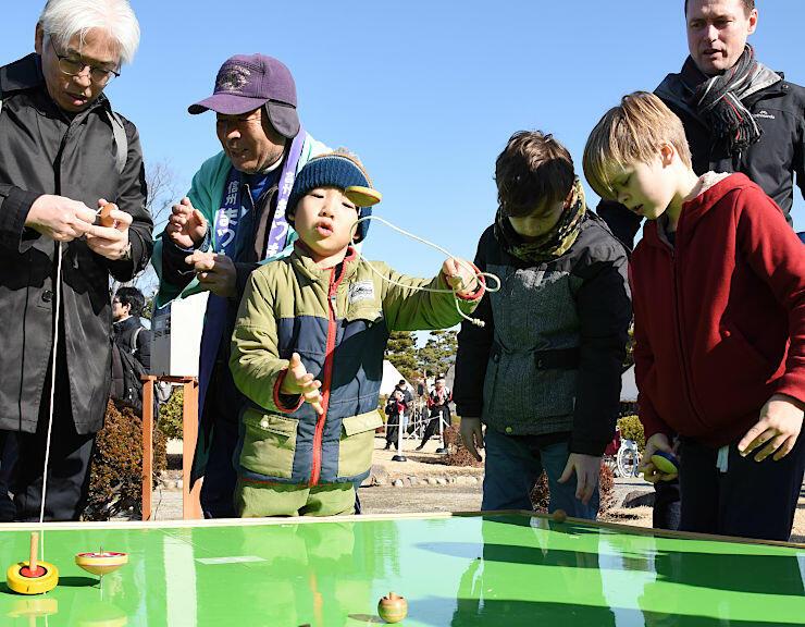 松本城本丸庭園でこま回しを楽しむ家族連れや観光客ら=3日、松本市