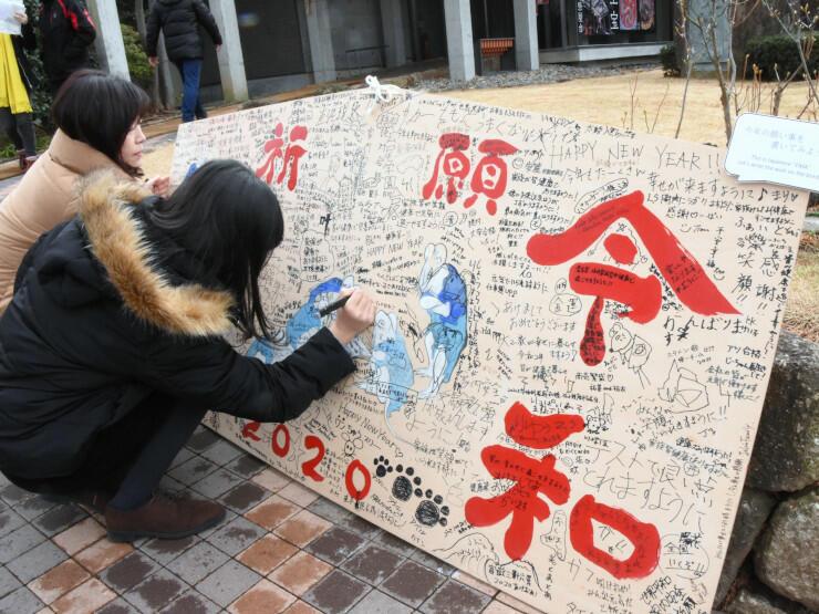市村さんが文字を書いた巨大絵馬に今年の抱負を書き込む観光客たち