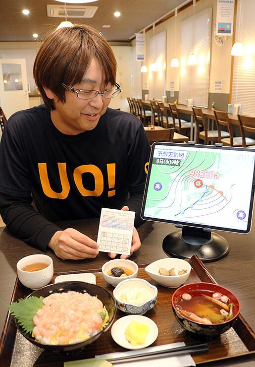 ポイントカードを紹介する竹内店長。食堂では甘エビむき身丼(手前)などが人気だ