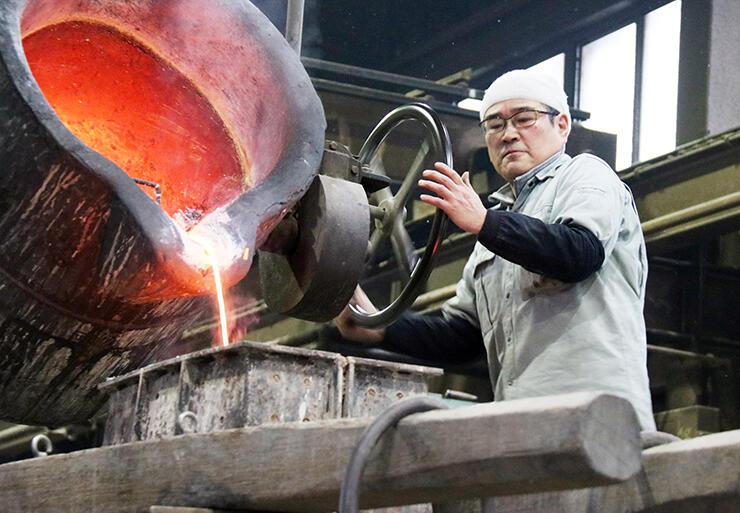 職人が取鍋のハンドルを慎重に回し、溶けた合金の量を調節する