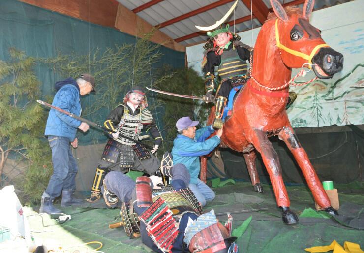 馬に乗った伊達政宗などの人形を仕上げる保存会の会員たち