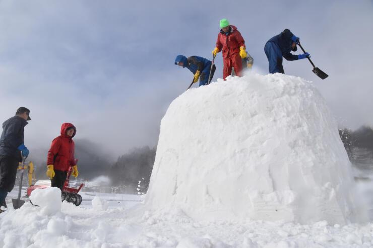 スコップで雪を固め、かまくらを造る応援隊員ら