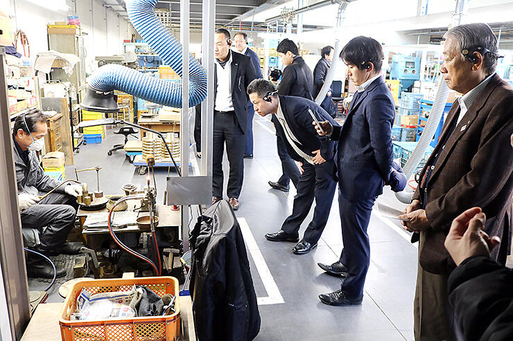 鋳物の仕上げ工程を見学する参加者