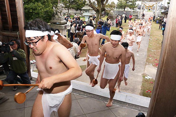 昨年の酒とり祭で、勢いよく拝殿を駆け上がる男性たち=2019年4月11日