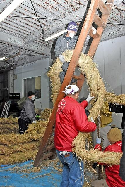 力を込めて3本の綱を編み上げ大綱を作る参加者=1月12日、福井県敦賀市相生町