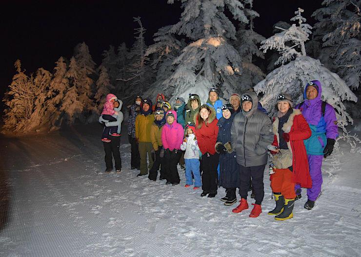 横手山山頂付近の樹氷群を背に記念撮影するナイトツアーの参加者ら=11日